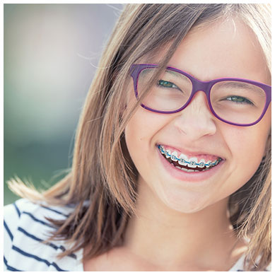 Little girl smiling with braces and glasses