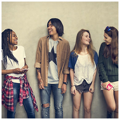Four teens leaning on wall talking to each other
