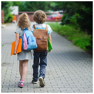 Young boy and girl walking to school while wearing backpacks